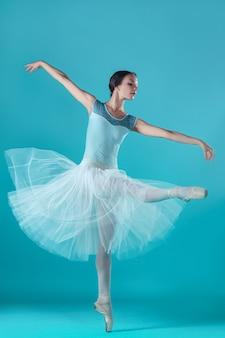 Ballerina in witte jurk die zich voordeed op de tenen