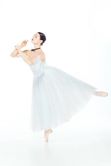 Ballerina in witte jurk die zich voordeed op pointeschoenen
