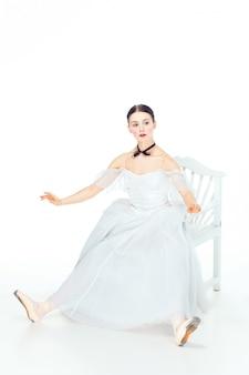 Ballerina in witte jurk zitten, studio ruimte.