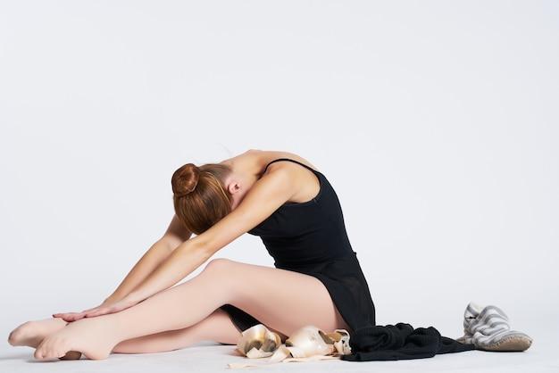 Ballerina in zwarte jurk die oefening uitvoert