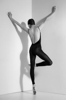 Ballerina in zwarte outfit poseren op pointe schoenen