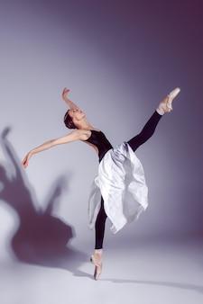 Ballerina in zwarte outfit poseren op tenen, studio achtergrond.