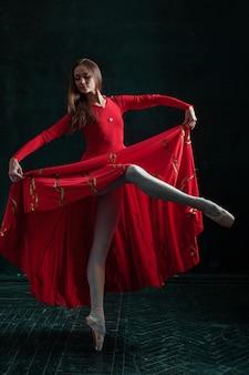 Ballerina poseren in pointe-schoenen op zwarte houten paviljoen
