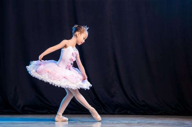 Ballerina van het meisje danst op het podium in witte tutu op pointe-schoenen klassieke variatie.