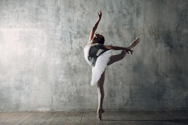 Ballerina vrouw. jonge mooie vrouw balletdanser, gekleed in professionele outfit, pointe schoenen en witte tutu.