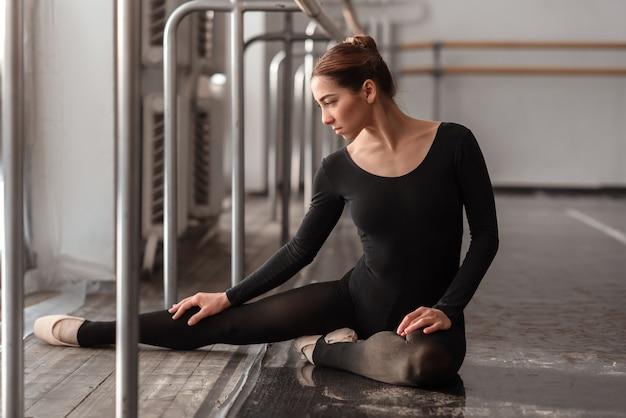 Ballerina zittend op de vloer in balletles
