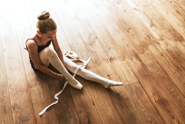 Ballerinaachtergrond, blond meisje dat schoenen op houten vloer bindt