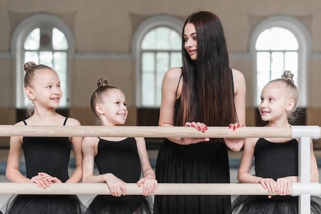 Ballerinameisjes met leraar die zich achter de staaf in dansklasse bevinden