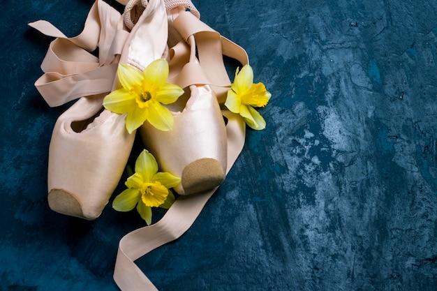 Ballerinaschoenen, pointe-schoenen zonder mensen op een blauwe achtergrond. bloemen van gele narcis. Premium Foto