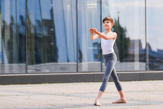 Ballet jongen tiener dansen tegen de achtergrond van de weerspiegeling van de stad en de lucht in de glazen wand