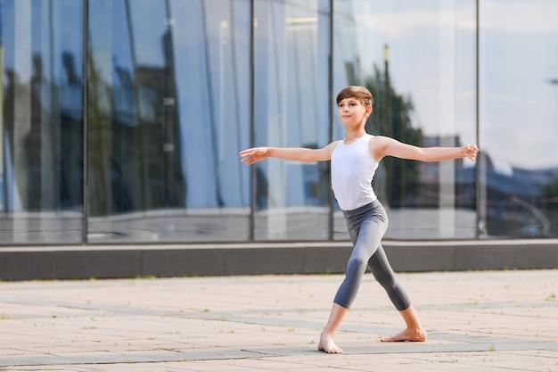 Ballet jongen tiener dansen tegen de achtergrond van reflectie van de stad en de lucht in de glazen wand