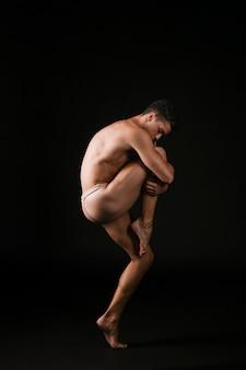 Balletdanser die hartstochtelijk knie omhelst