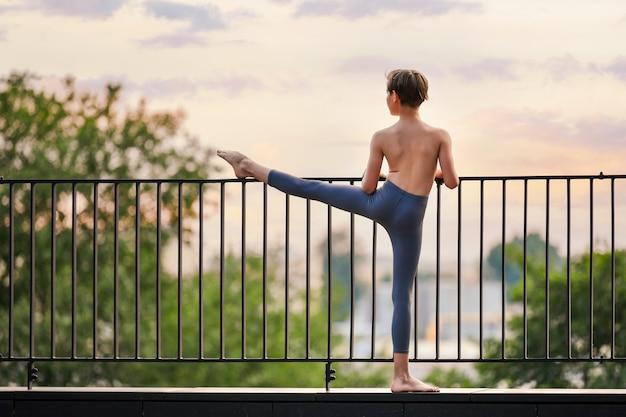 Balletdanser tiener jongen oefenen op het dak van de stad zonsondergang hemelachtergrond