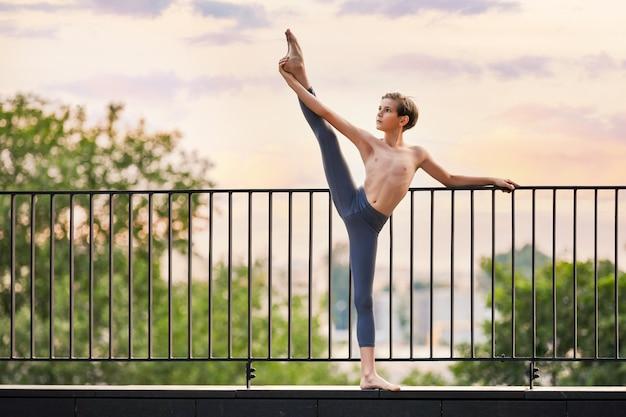 Balletdanser tiener jongen oefenen op het dak zonsondergang hemelachtergrond