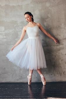 Balletdansereballerina in het mooie lichtblauwe de rok van de kledertutu stellen in zolderstudio