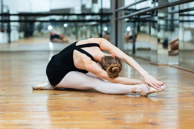 Balletdanseres uitvoeren van oefening zittend op de vloer