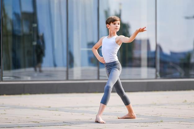 Balletjongen dansen tegen de achtergrond van reflectie van de stad in de glazen wand