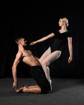 Balletpaar die in maillot met exemplaarruimte dansen
