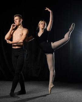 Balletpaar poseren in balletuitrustingen