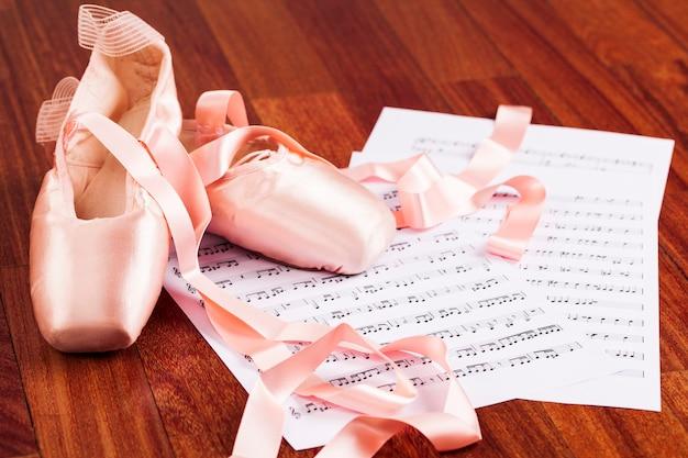 Balletschoen op een houten vloer over een muziekscore.