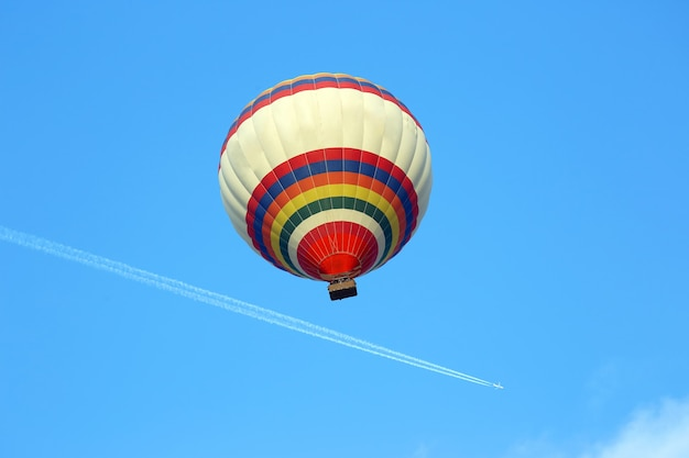 Ballon die in de lucht op de achtergrond van een vliegend vliegtuig vliegt