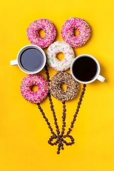 Ballon met donuts en kopjes koffie op gele achtergrond