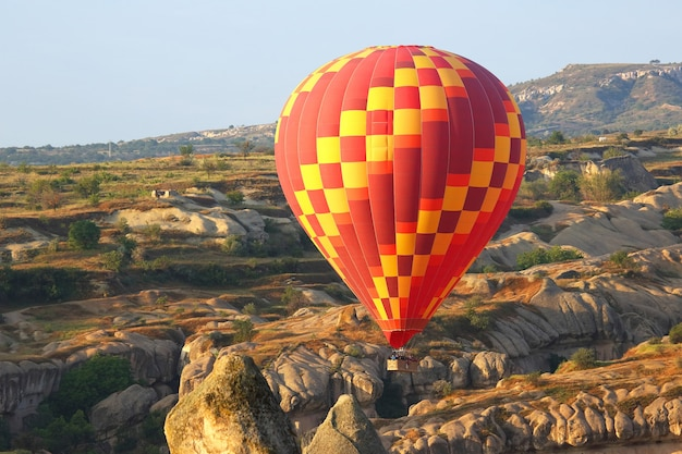 Ballon vliegt in bergachtig gebied in cappadocië