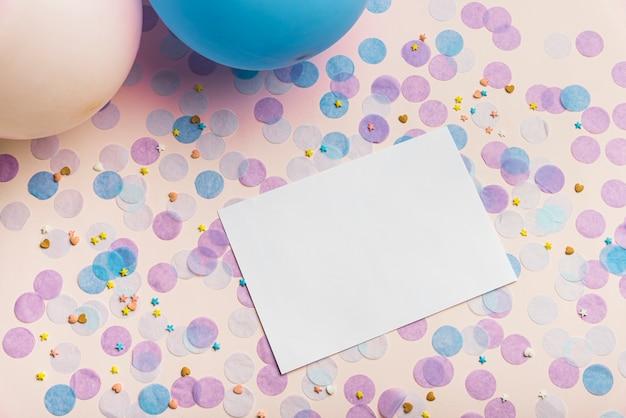 Ballonnen en confetti op gele achtergrond met kopie ruimte