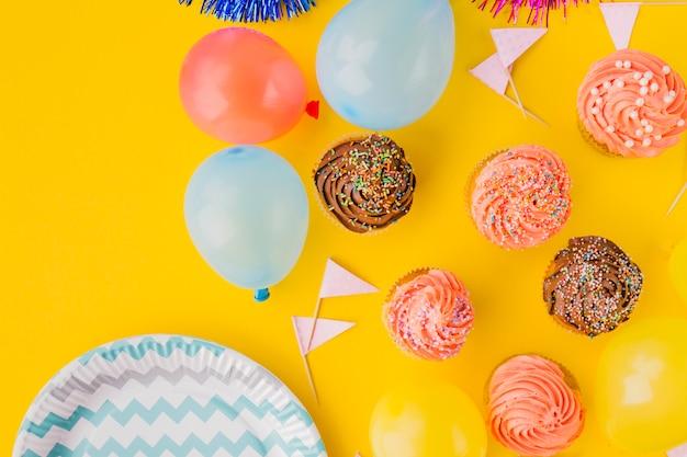 Ballonnen en cupcakes in de buurt van plaat