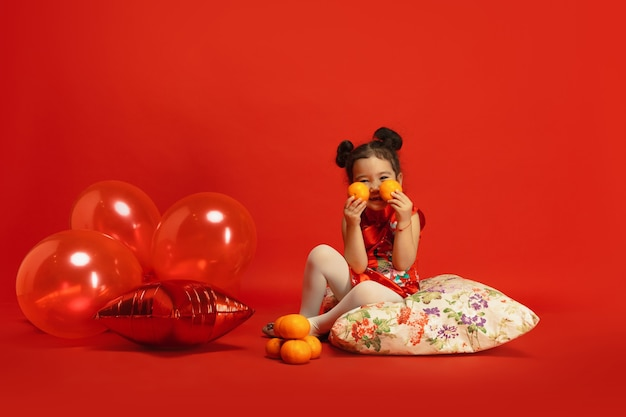 Ballonnen en mandarijnen voor gemoedstoestand. leuk poseren. aziatisch schattig klein meisje geïsoleerd op rode muur in traditionele kleding. viering, menselijke emoties, vakantie. copyspace.