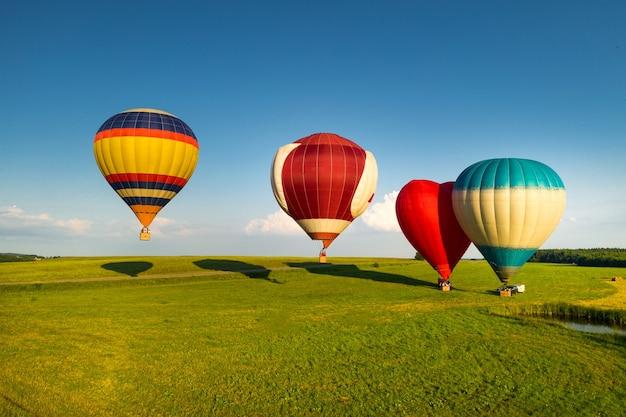 Ballonnen met mensen staan klaar om op te stijgen in het veld.