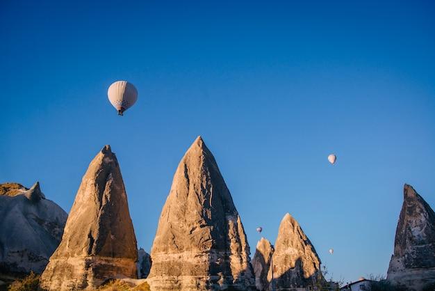 Ballonnen vliegen over scherpe rotsen in cappadocië