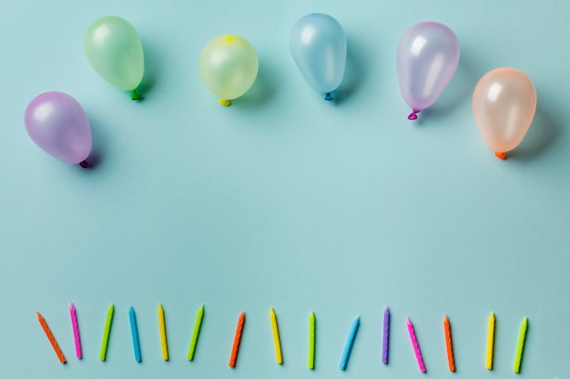 Ballons over de rij van kleurrijke kaarsen tegen blauwe achtergrond