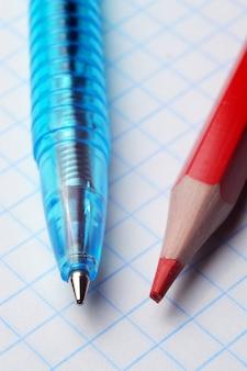 Balpen en rood potlood liggen op een vel van een notitieboekje in een doos. detailopname.