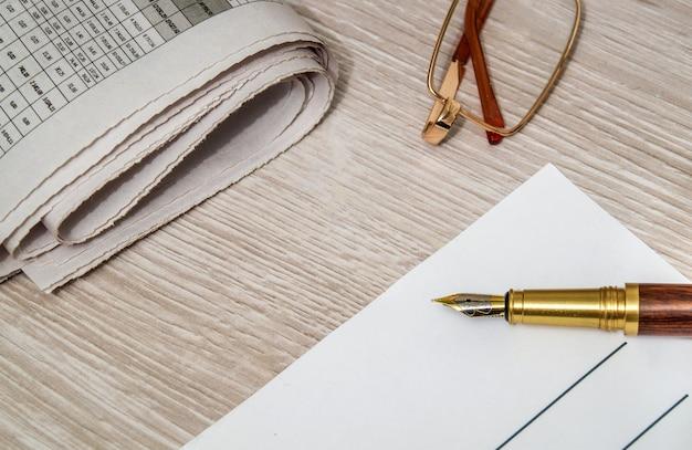 Balpen om op een vel papier te schrijven en een bril om de krant te lezen
