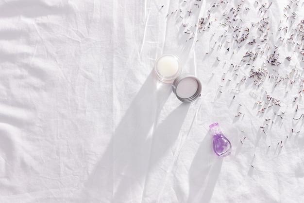 Balsem met etherische olie van lavendel en droge bloemen met schaduwen op wit beddengoed