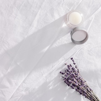 Balsem met etherische olie van lavendel en droge bloemen op wit beddengoed. de geur van lavendel verbetert de slaap en verlicht slapeloosheid. prachtig avondlicht.
