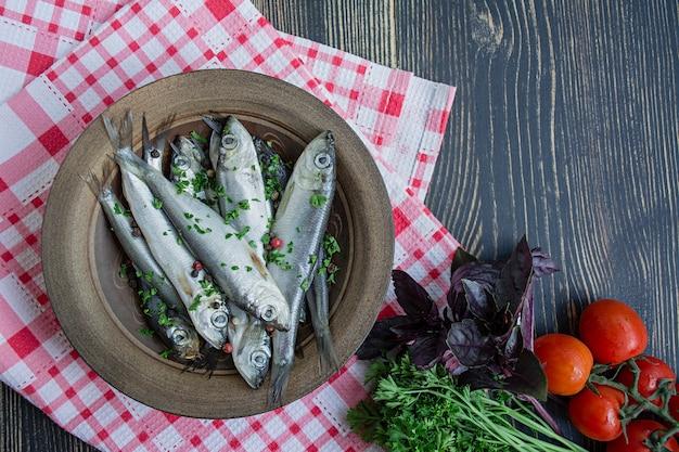 Baltische haringzeevruchten. gezouten haring vis in een kom met specerijen en kruiden.
