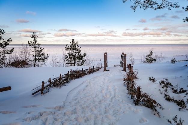 Baltische zee houten trappen die leiden naar de bevroren zee besneeuwd winterlandschap