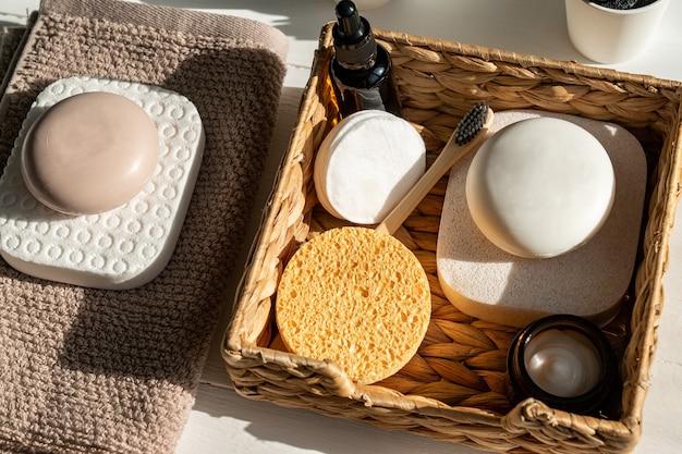 Bamboe accessoires voor badkuip, zeepstaven, borstels, tandenborstel, handdoek en biologische gezichtsolie voor persoonlijke hygiëne.