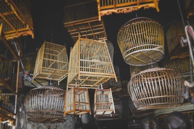 Bamboe mandenmakerij vogelkooi stockwinkel met weinig licht binnenshuis.