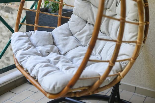 Bamboe stoel met grijs kussen hangend aan het balkon