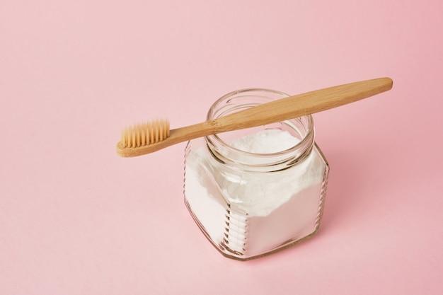 Bamboe tandenborstel en frisdrank in pot op roze achtergrond kopie ruimte