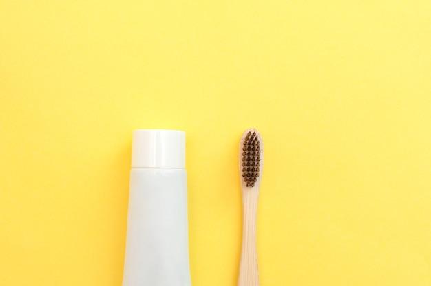 Bamboe tandenborstel en tube pasta op een gele achtergrond. tandheelkunde.