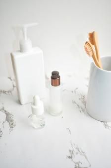 Bamboe tandenborstel, gezicht serums op een marmeren tafel