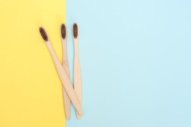 Bamboe tandenborstel op een gele en blauwe achtergrond. kopieer ruimte