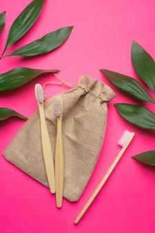 Bamboe tandenborstels en een canvas tas op een roze achtergrond