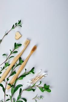 Bamboe tandenborstels en oordopjes, en groene bladeren, eco-vriendelijke, zero waste producten voor persoonlijke hygiëne, concept voor tandverzorging