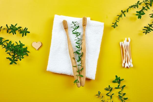 Bamboe tandenborstels en oordopjes met handdoek en groene bladeren, eco-vriendelijke, zero waste producten voor persoonlijke hygiëne, tandheelkundige zorgconcept