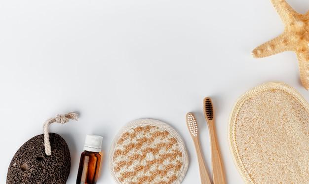 Bamboe tandenborstels, gezicht en lichaam sponzen, etherische olie en puimsteen op wit